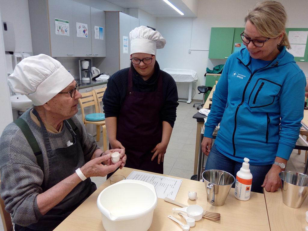 Kuntoutuja leipoo, opiskelija ja opettaja kannustavat
