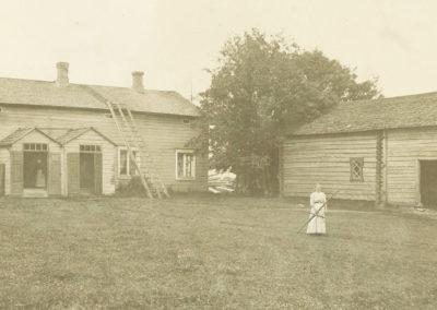 Vanhassa valokuvassa Bovalliuksen kartanon rakennusten edessä nainen ja piilossa ovensuun pimeydessä toinen sisaruksista.