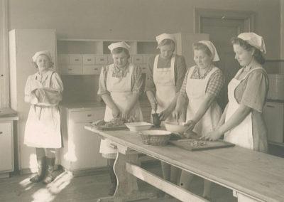 Valkoisiin essuihin ja päähineisiin pukeutuneet tytöt ja keittäjä tekevät ruokaa pirtinpöydän ääressä.