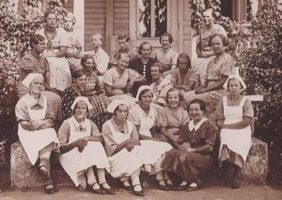 Mustavalkoisessa ryhmäkuvassa etualalla olevilla oppilailla on valkoiset essut ja päähineet, muut tytöt ovat pukeutuneet mekkoihin.