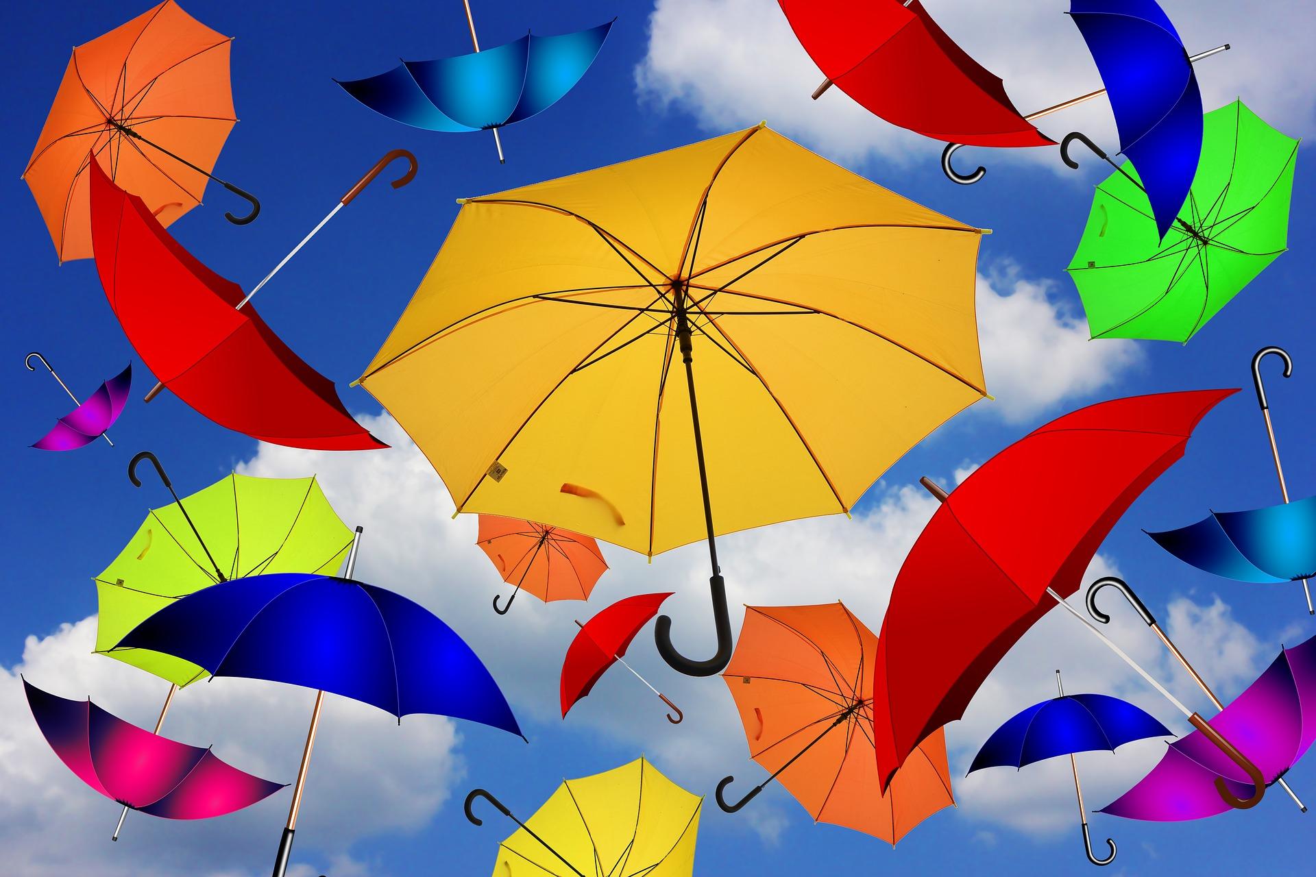 Värikkäitä sateenvarjoja leijumassa taivaalla