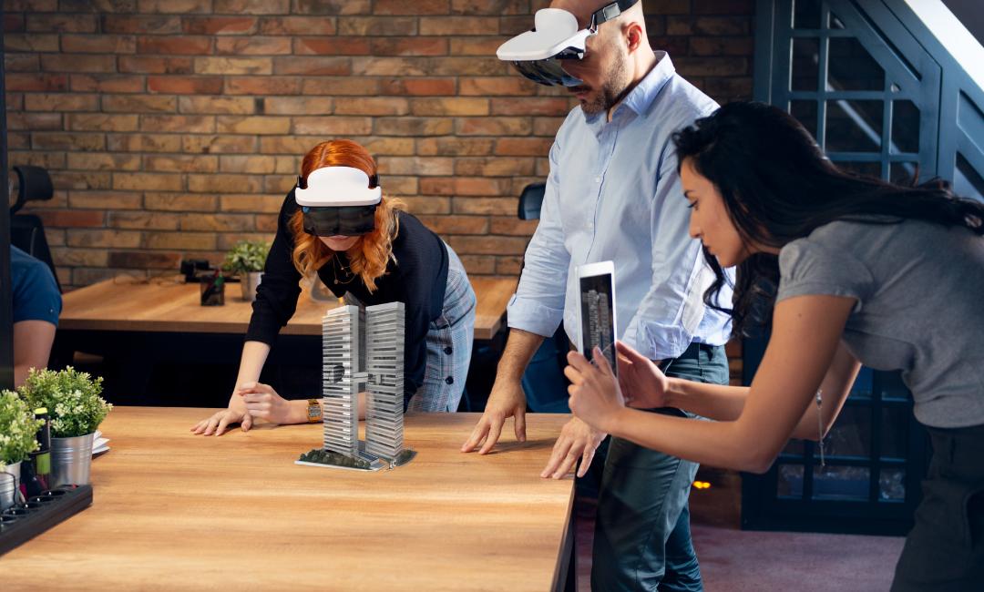 Kuvakaappaus ARVET-hankkeen www-sivulta, kuvassa yksi henkilö kuvaa esinettä ja kaksi henkilöä seuraa vierestä VR-lasit päässä.