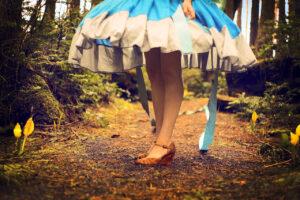 vyötäröstä alaspäin kuvattu nainen metsämaisemassa, naisella yllään Liisa ihmemaassa -tyylinen sinivalkoinen mekko.