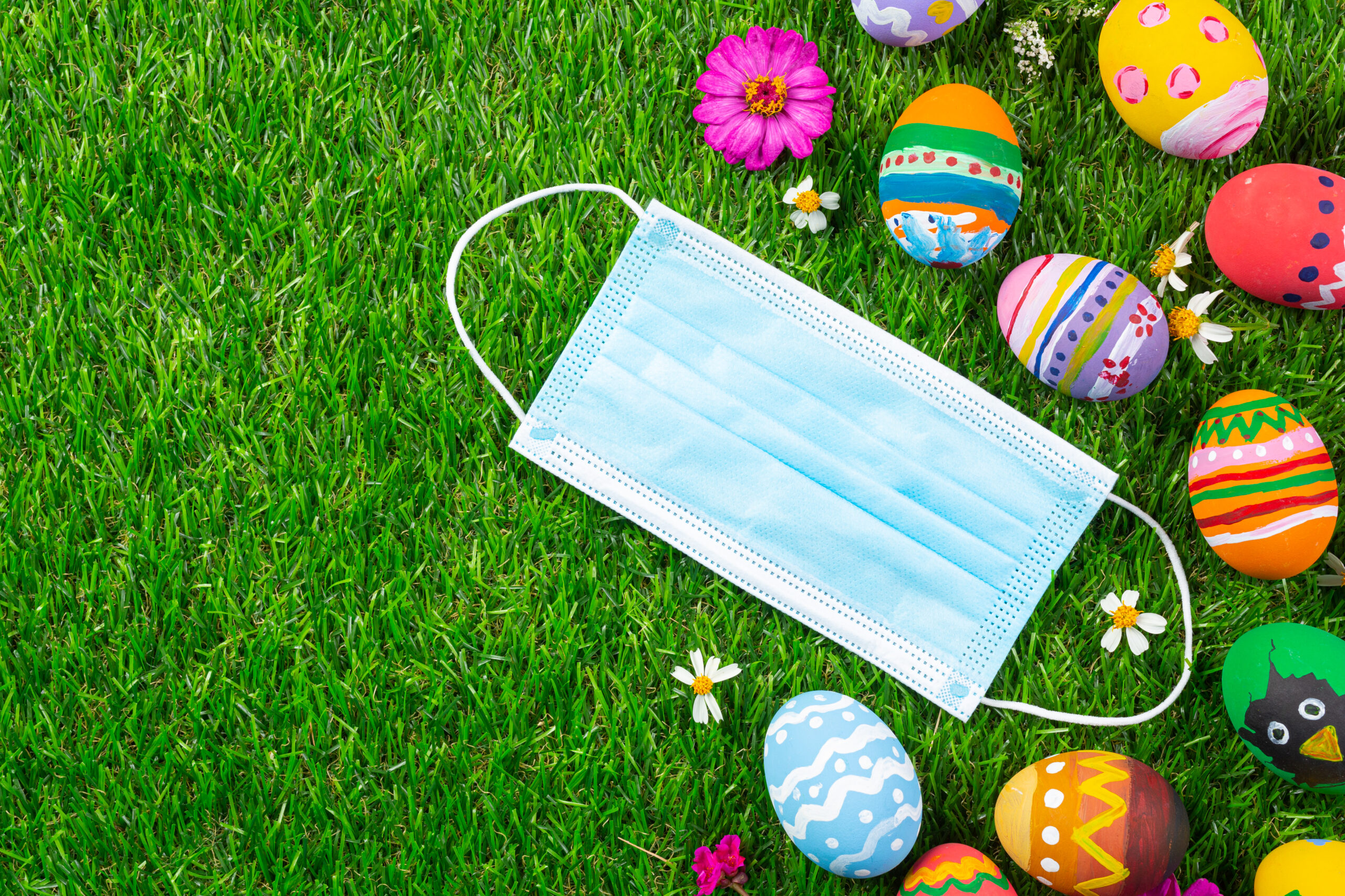 värikkäitä pääsiäismunia ja käyttämätön maski nurmikolla