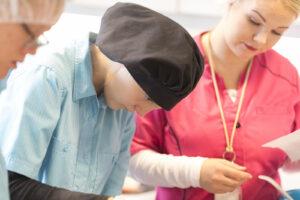 Opiskelija työskentelee keskittyneesti keittiöllä, ohjaaja seuraa vieressä.