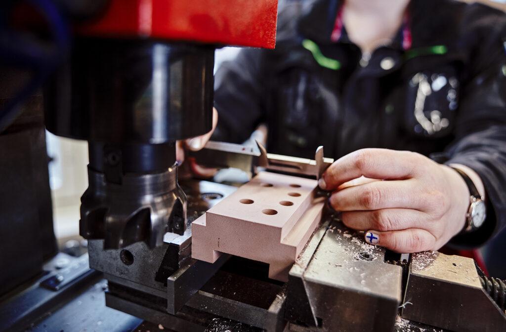 Lähikuvassa työstökone, kädet ja kappaleen mittaus työntömitalla.