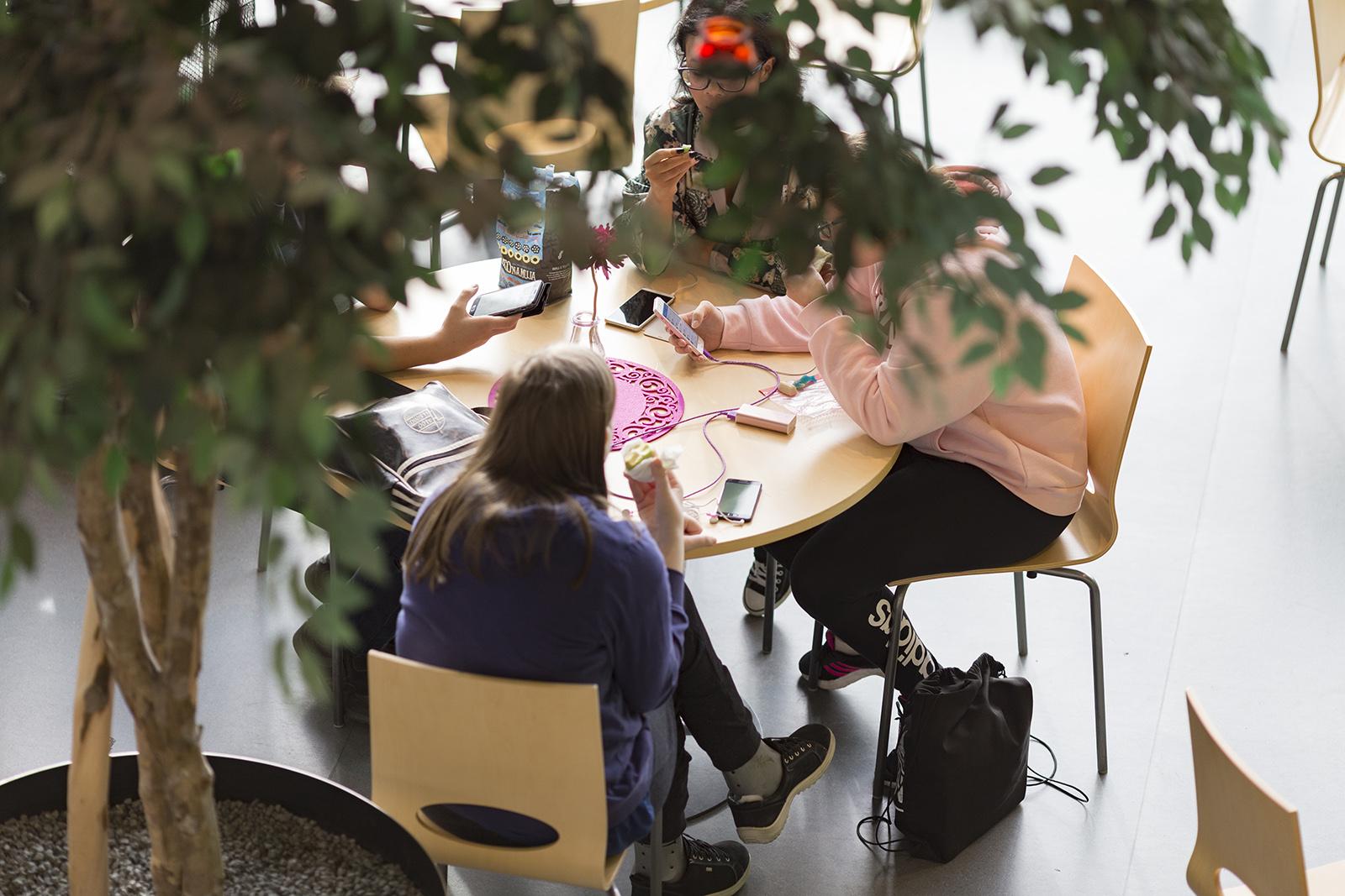 Opiskelijoita pöydän ääressä välipalalla, yläviistosta etäältä kuvattuna.