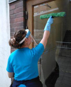 Tiia Peippo puhdistaa rappukäytävän ovilasia ulkopuolelta.