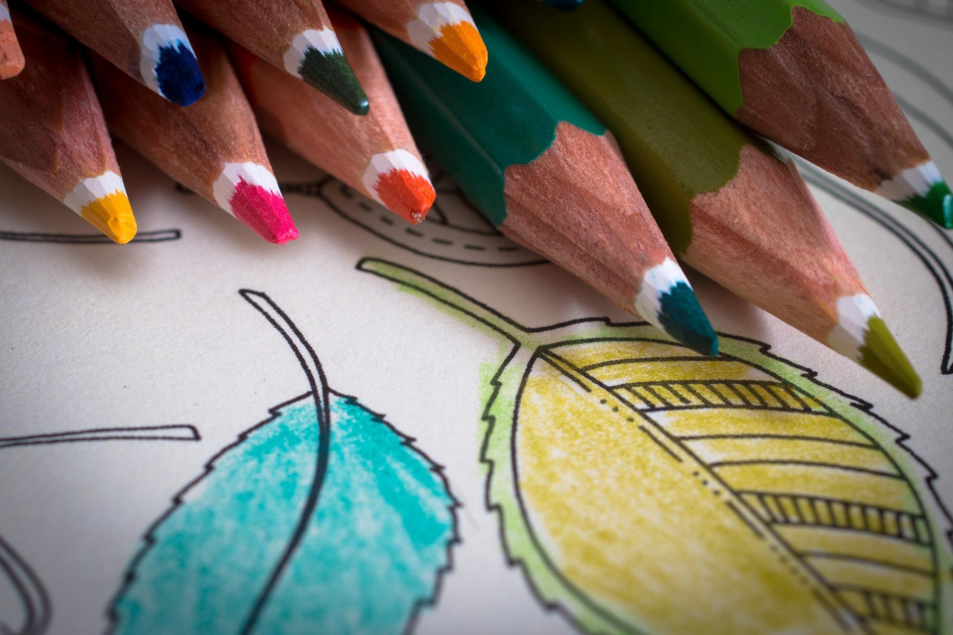 Eri värisiä värikyniä hiukan jo väritetyn värityskirjan sivun päällä.