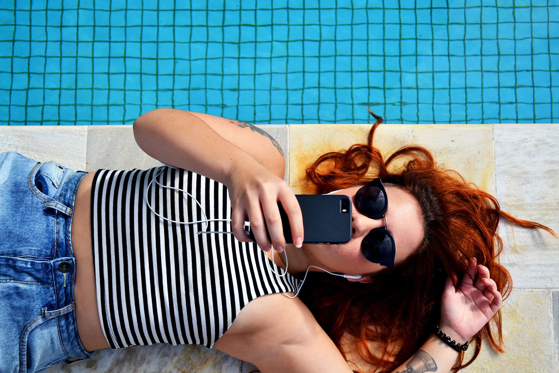 Nainen rentoutuu uima-altaan äärellä kännykkä kädessään.