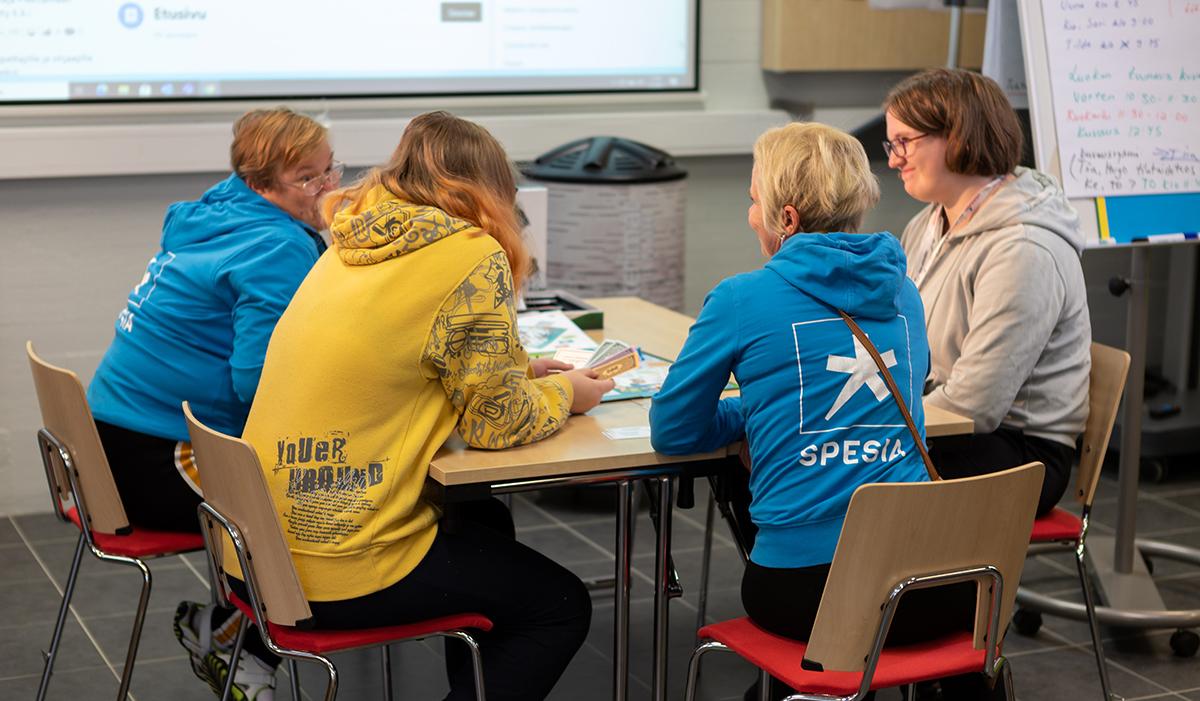 Opettaja Susanna Luhtala, ohjaaja ja kaksi opiskelijaa keskustelevat pöydän ääressä.
