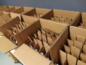 Pitkä rivi avonaisia pahvilaatikoita, joiden sisällä on pienempiä pahvipakkauksia.