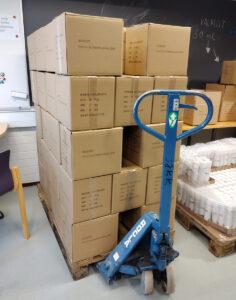 Pino valmiiksi pakattuja laatikoita hulissa eli vetokärryssä.